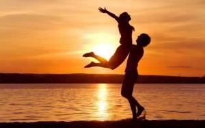 Парня и девушки на закате солнца пляж